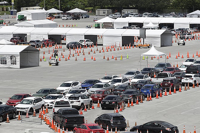 Lines of cars wait at a coronavirus testing site outside of Hard Rock Stadium, Friday, June 26, 2020, in Miami Gardens, Fla. Florida banned alcohol consumption at its bars Friday as its daily confirmed coronavirus cases neared 9,000, a new record that is almost double the previous mark set just two days ago. (AP Photo/Wilfredo Lee)