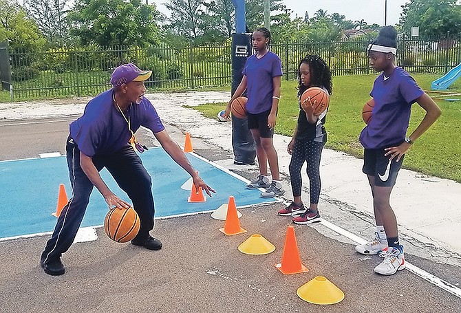COORDINATOR Terrance 'Red Eye' McSweeney shows Raven Jones, Marcia Hall and Jasmin Roker how to dribble the ball.
