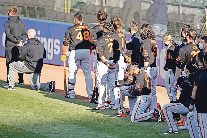 SAN Francisco Giants' Antoan Richardson (00) and Jaylin Davis kneel during the national anthem prior to an exhibition baseball game against the Oakland Athletics on Monday in Oakland, California.  (AP Photo/Ben Margot)