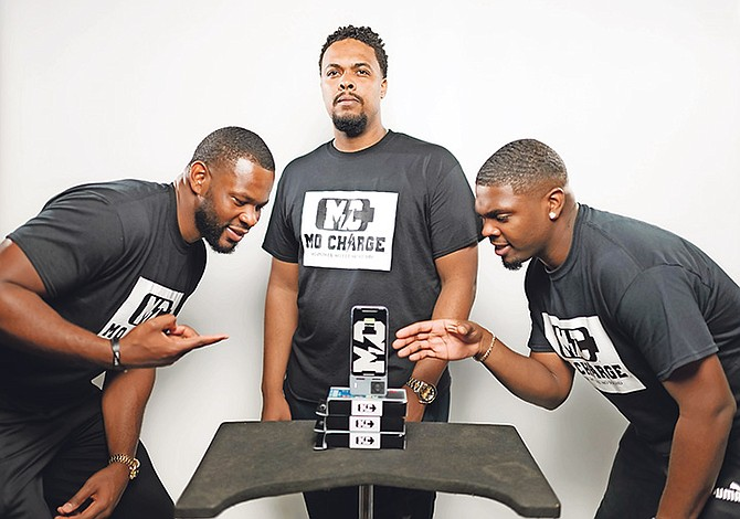 NORTH Andros pro basketball player Shaq Cleare and his cousins Micah and Christen Miller display their phone chargers.