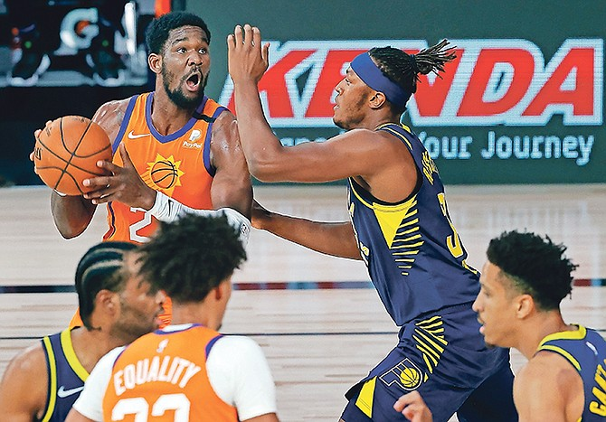 Phoenix Suns' Deandre Ayton (22) drives to the basket as Indiana Pacers' Myles Turner (33) defends during the first half of an NBA basketball game Thursday, Aug. 6, 2020, in Lake Buena Vista, Fla. (Kevin C. Cox/Pool Photo via AP)