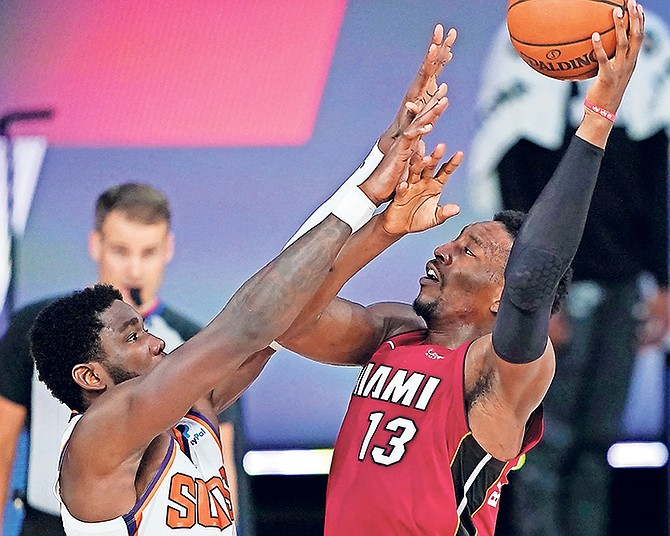Heat's Bam Adebayo (13) is fouled by Suns' Deandre Ayton during the second half on Saturday night in Lake Buena Vista, Florida.  (AP Photo/Ashley Landis)