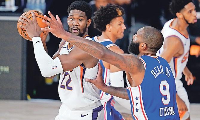 Phoenix Suns centre Deandre Ayton (22) looks for help as Philadelphia 76ers centre Kyle O'Quinn (9) applies pressure during the second half yesterday in Lake Buena Vista, Florida.  (AP Photo/Ashley Landis)