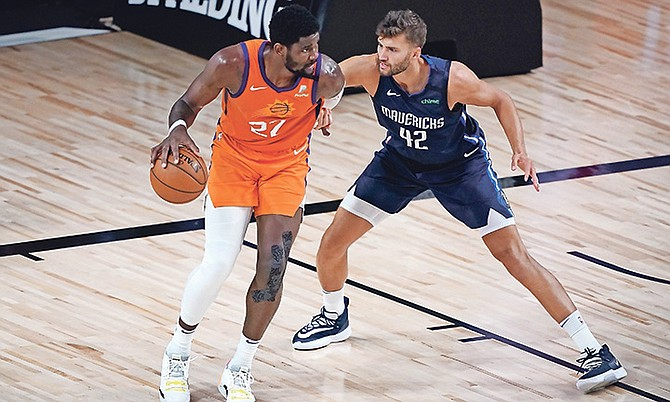 Suns' Deandre Ayton, left, dribbles as Mavericks' Maxi Kleber (42) defends.  (AP Photos/Ashley Landis)