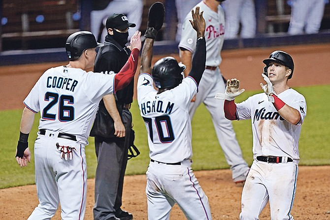 Miami Marlins' Garrett Cooper (26), Jazz Chisholm (70) and Corey Dickerson, right, celebrate after they scored on a double by Starling Marte during the eighth inning of a baseball game against the Philadelphia Phillies, Thursday, in Miami. (AP Photo/Wilfredo Lee)