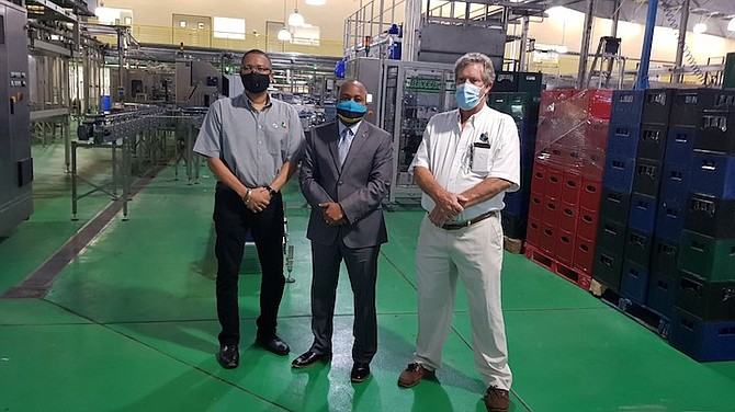 Senator Kwasi Thompson (centre) stands in the newly renovated and expanded warehouse at Bahamian Brewery, during a tour of the facility on Friday. Standing with Mr Thompson is James Sands, president of Bahamian Brewery (right) and Ian Rolle, president of the Grand Bahama Port Authority.  (BIS Photo/Andrew Coakley)