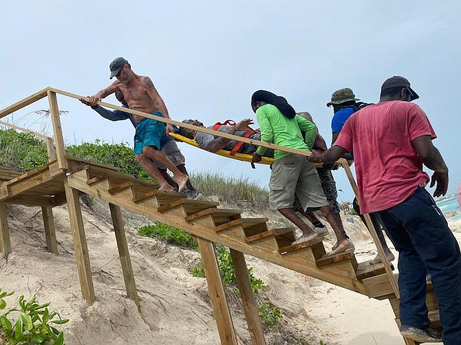 ROYAL Bahamas Defence Force Marines, police and local community members rescue a man who was partially buried under the sand on Saturday. Photo: Able Seaman Michael Turner II/RBDF