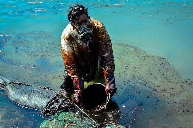 "A MAN scoops leaked oil from the vessel MV Wakashio, belonging to a Japanese company that ran aground near Blue Bay Marine Park off the coast of south-east Mauritius on August 2, 2020. ""As soon as you go south of Mauritius, you start smelling the oil. Within a short time you have a headache and, if you are near the coast, you quickly become ill…"""