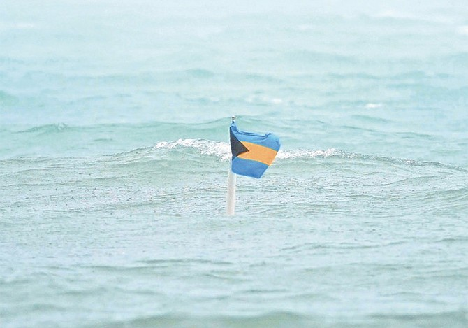 A BAHAMAS flag flutters above the flood waters . . . just. Photo: Terrel W Carey Sr/Tribune Staff