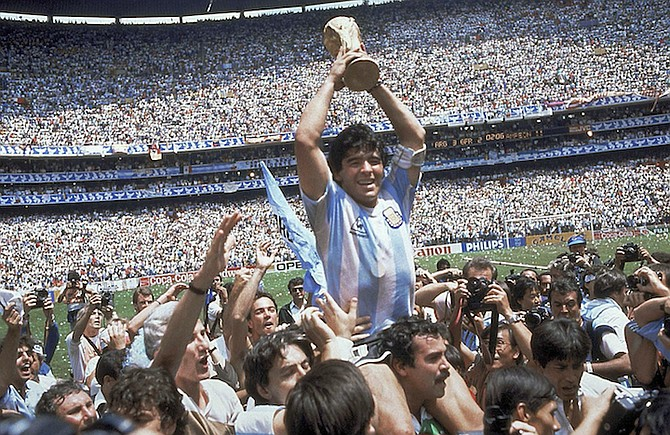 Diego Maradona holds up his team's trophy after Argentina's 3-2 victory over West Germany at the World Cup final in the Azteca Stadium in Mexico City in 1986. (AP Photo/Carlo Fumagalli, File)