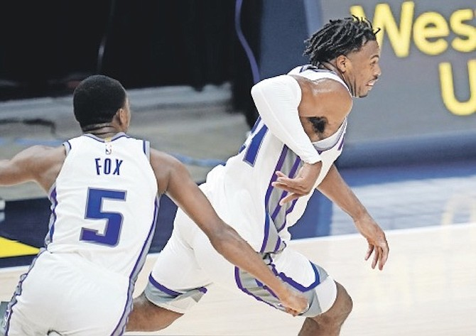 SACRAMENTO Kings guard Buddy Hield, right, reacts after putting in the winning basket in overtime against the Denver Nuggets last night in Denver. Sacramento guard De'Aaron Fox is at left.  (AP Photo/David Zalubowski)