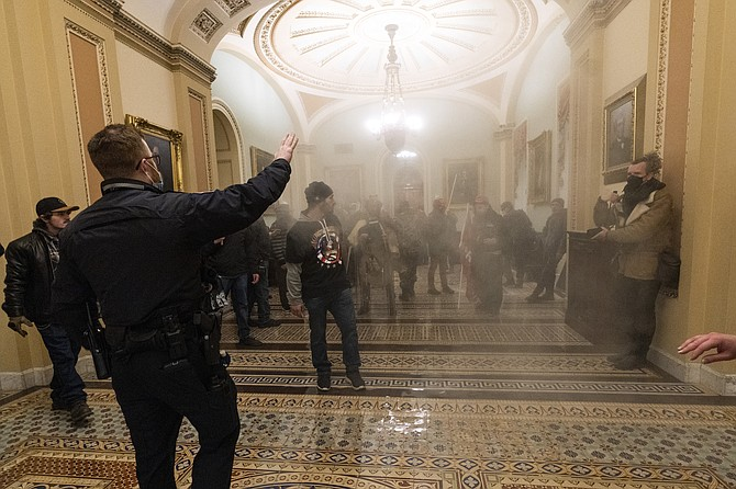 Smoke fills the walkway outside the Senate Chamber as supporters of President Donald Trump are confronted by U.S. Capitol Police officers inside the Capitol, Wednesday, in Washington. (AP Photo/Manuel Balce Ceneta)