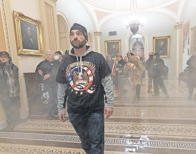 SMOKE fills the walkway outside the Senate Chamber as supporters of President Donald Trump are confronted by US Capitol Police officers inside the Capitol on January 6. Photo: Manuel Balce Ceneta/AP