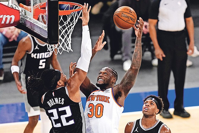Knicks forward Julius Randle (30) shoots against Sacramento Kings centre Richaun Holmes (22) in the second half last night in New York. Buddy Hield can be seen at right.