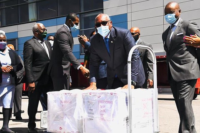 Prime Minister Dr Hubert Minnis with the vaccines after they arrived in the country on Wednesday. Photo: Yontalay Bowe
