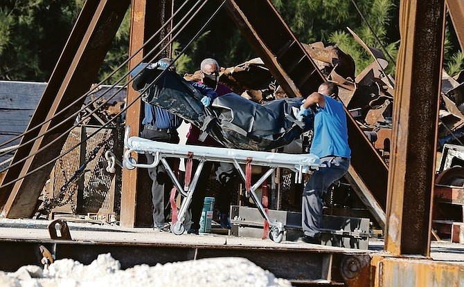 A body is taken from the scene at City Services Ltd yesterday after three men died.  Photo: Vandyke Hepburn